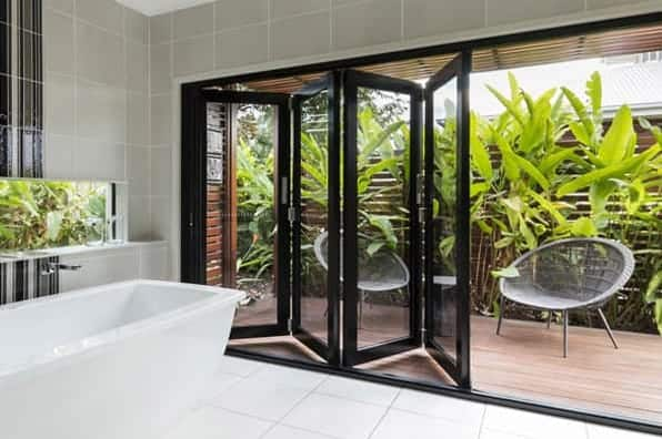 modern aluminium bifold doors opening up to courtyard