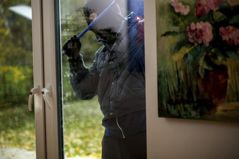 burglar trying to break open a door using a crowbar